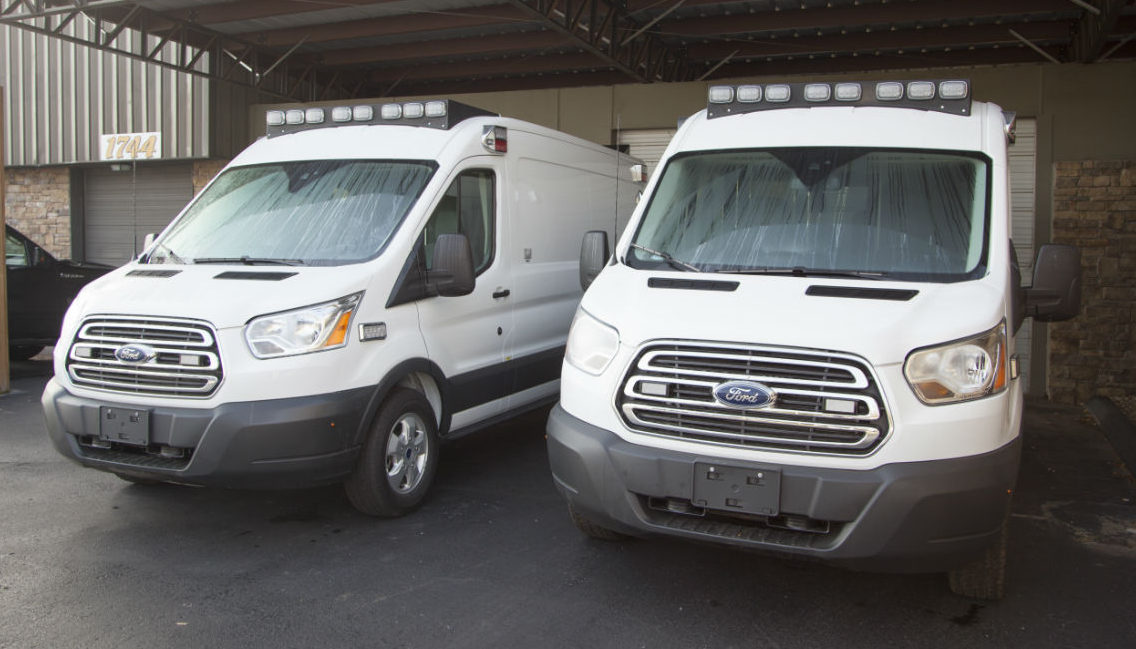 Two Type II Ford Transit Midroof Vehicles side by side